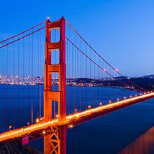An illuminated and bright red Golden Gate Bridge at night.